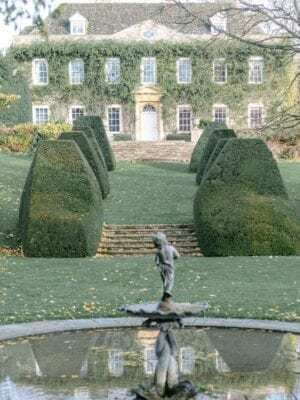 Claire Graham Cornwell manor gardens pond with hedges and view of the manor in the background