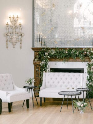 Beautifully decorated fireplace with white chairs and candles