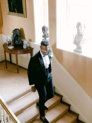Groom walking down the stairs in suit and bowtie