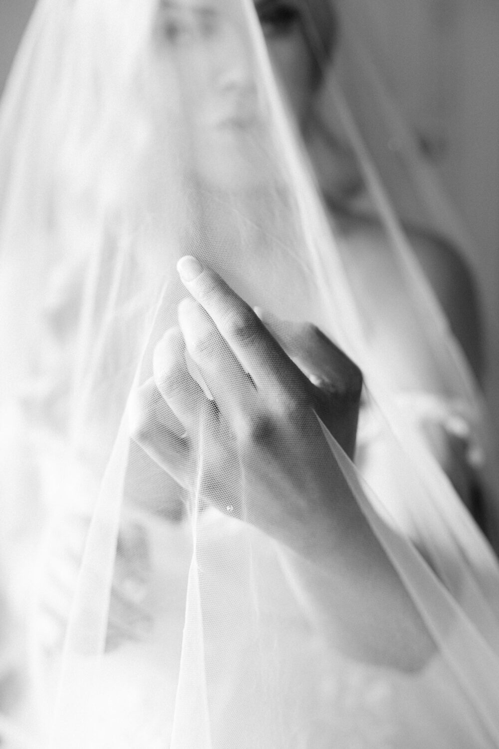 black and white picture of a Bride putting her hand through her veil