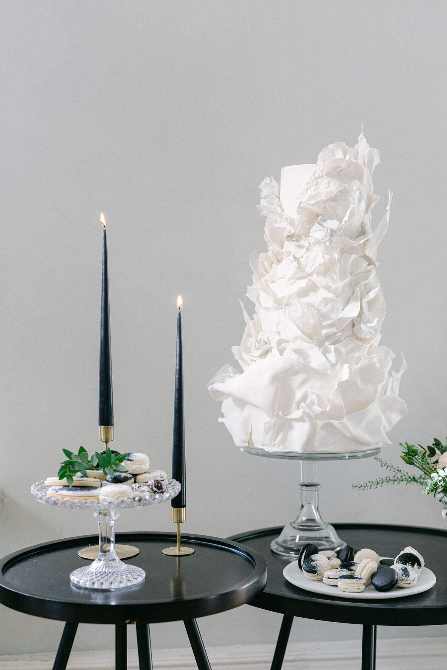 White wedding cake on black round tables with candles lit - elegant wedding planner surrey