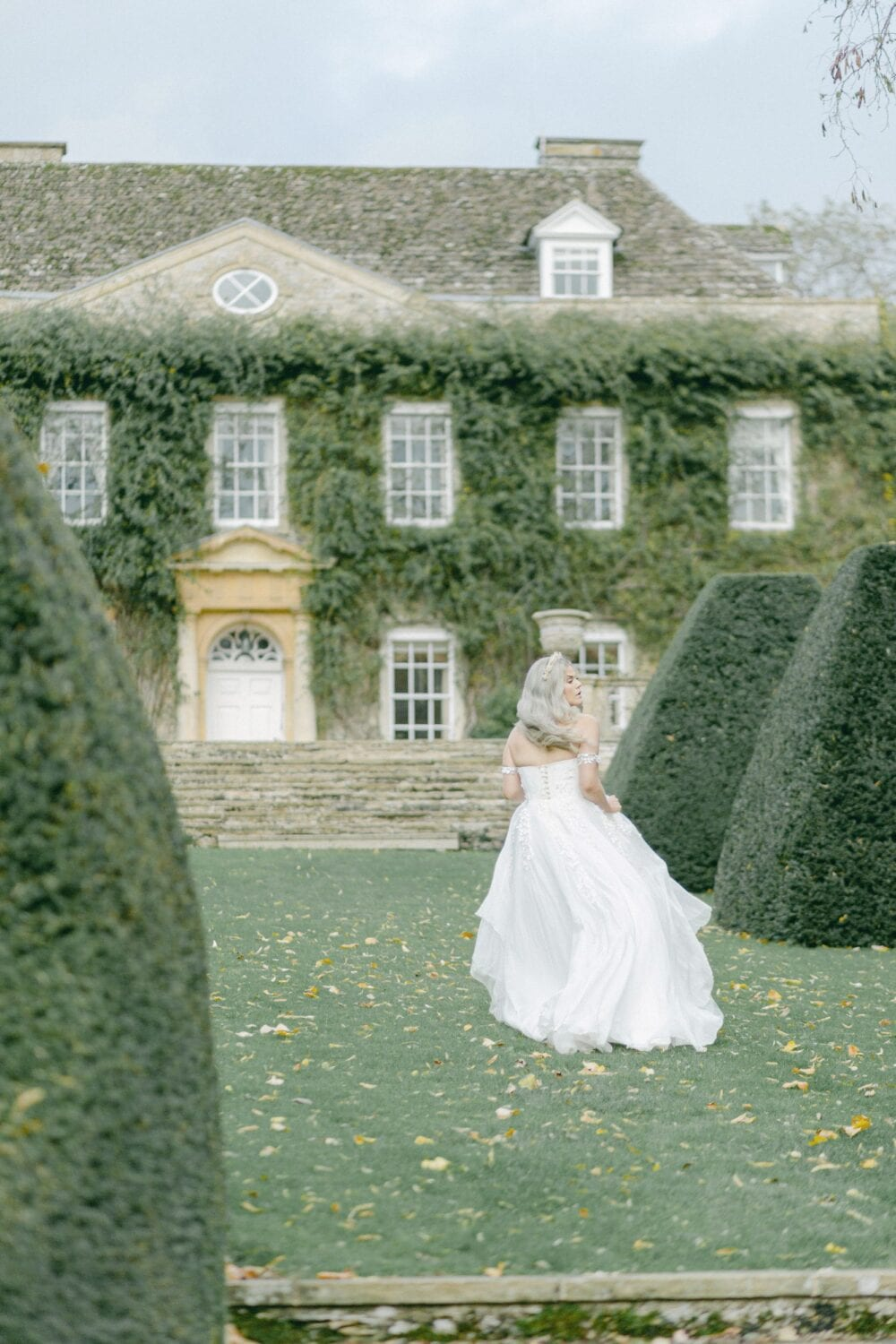 woman in dress walking in the garden near hedges amazing wedding planner - parties celebrations surrey