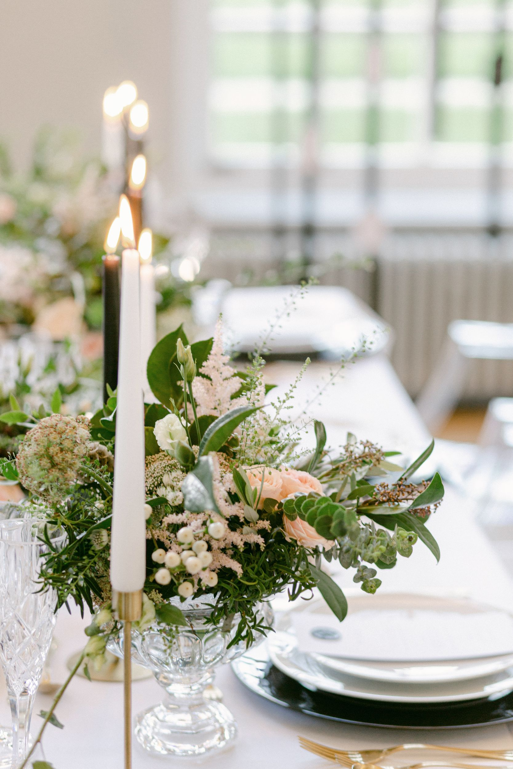 lit candles on a wedding table with green and white flowers Wedding table bouquet designed by Amie Jackson - modern wedding planner surrey